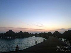 Pôr-do-sol visto do deck entre os bangalôs.